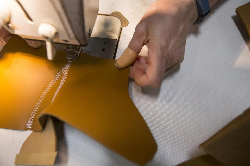 A bootmaker sewed pieces together to make the top of the Bean Boot.